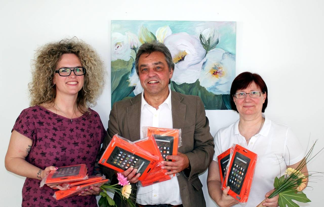 Bild copyright: Amazon Kindle MGH  Bildunterschrift: Maria Mench (l.) und Marion Bolender vom Amazon-Logistikzentrum übergaben die acht Kindle-Geräte an einen sichtlich erfreuten Fachbereichsleiter Edgar Steube